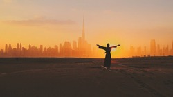 Arabic woman weared in traditional UAE dress - abayain rising her hands on the sunset at a desert with Dubai city silhouette on the background.