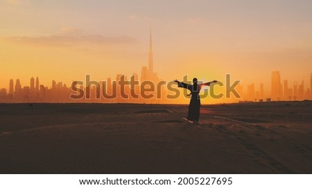 Arabic woman weared in traditional UAE dress - abayain rising her hands on the sunset at a desert with Dubai city silhouette on the background. Stockfoto ©
