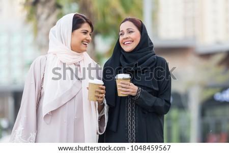 Arabic women shopping outdoors in Dubai - Girls with traditional arabian dress having fun