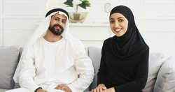 Arabs muslim happy couple talking to camera, waving with hands. Having videochat. Male and female Arabians videochatting on webcam. Middle East. Male in kandura and woman in hijab. Traditional outfits