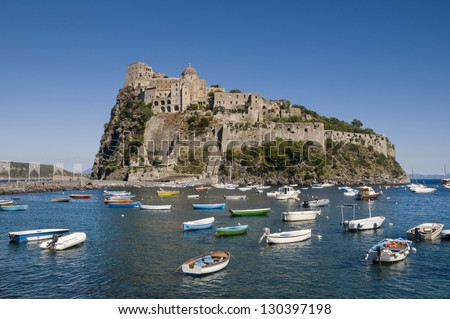 Aragonese castle in Ischia, a little island in the bay of Naples, Italy. Many little boats moored in the cove in front of it