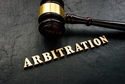 Arbitration word from wooden letters and gavel in court.