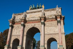 Arc de Triomphe du Carrousel (Triumphal Arch at Carrousel Place) monument is a tribute to Napoleon's military victories in Paris, France on an autumn day with clear blue sky