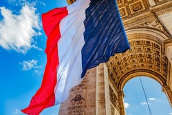 Arc de Triomphe French Flag Paris France. Completed in 1836 monument to the dead in the French Revolution and Napoleonic Wars. Includes tomb to unknown soldier
