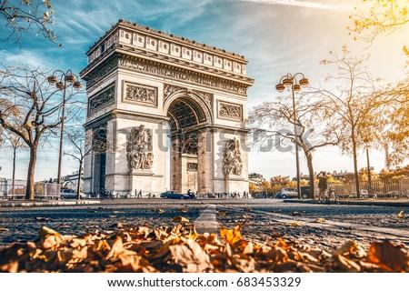 Arc de Triomphe located in Paris, in autumn scenery.