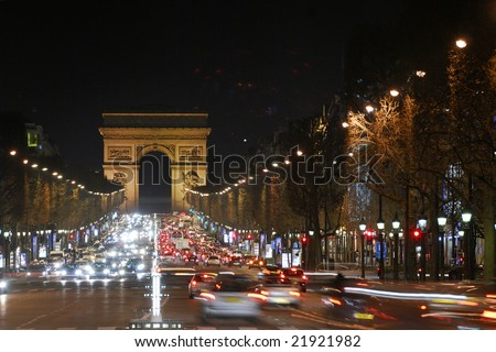 Arc de Triomphe, Paris. Illuminated avenue Champs Elysees by night. Cars traffic