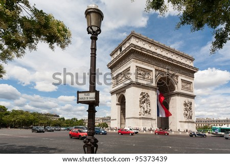 Arc de Triomphe with lamppost in foreground showing the full roundabout