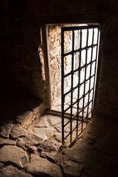 Arc fort passageway from cold damp Blackness to glow Light with rusted iron grate cell. Gaol rugged ominous shadow solid hallway with upward leading to day sunlight with space for text on sky backdrop