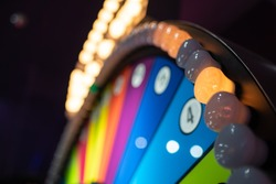 Arcade gambling machine up close. Giant wheel with colorful sections and lights.