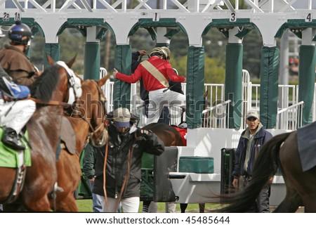 ARCADIA, CA - 7 FEB 09: Jockeys and horses are loaded into the gate to start a race at Santa Anita Park on Feb 7, 09, in Arcadia, CA.