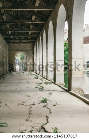 arch along the building, under the arches, a long cracked cement path #1145107817