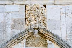 Arch and heraldic shield of the main entrance. Ruins of the Royal Monastery of Santa María de Nogales. San Esteban de Nogales, León, Spain.