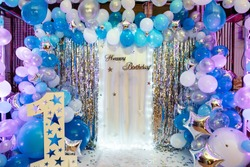 Arch blue, white and silver balloons decorate the party. Festive decorative elements, photo area. Birthday decorations with photo area, balloons, garlands and number one for a small children's party
