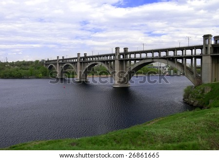 Arch bridge on a dark river with green banks