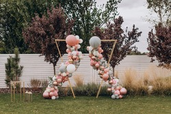 Arch for a wedding exit ceremony, made of balloons, gray, white, gold and pink in different sizes.