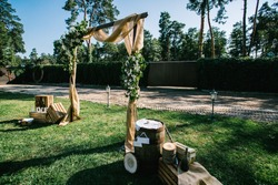 Arch for ceremony a is decorated with flowers and greens. Wedding decor. Wooden barrel. Wooden plaque with the inscription Mr and Mrs. Decorations signboard against the background of wooden box.