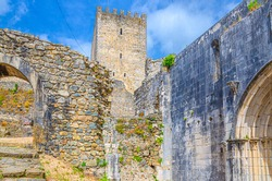 Arch in stone wall and bell tower of medieval Castle of Leiria Castelo de Leiria building in historical city centre, Portugal