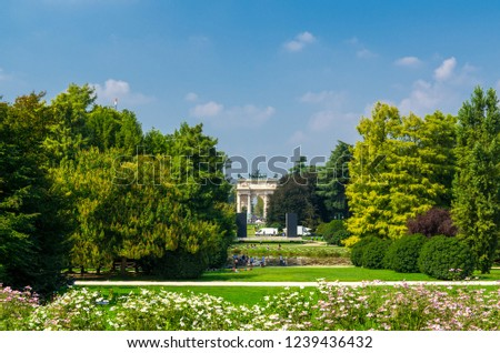 Arch of Peace Arco della Pace gate and green trees, flowers, grass lawn in Parco Sempione park with blue sky background in Milan city centre, Lombardy, Italy