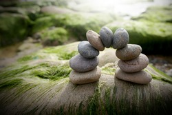 Arch of pebbles in balancing on the mossy rock