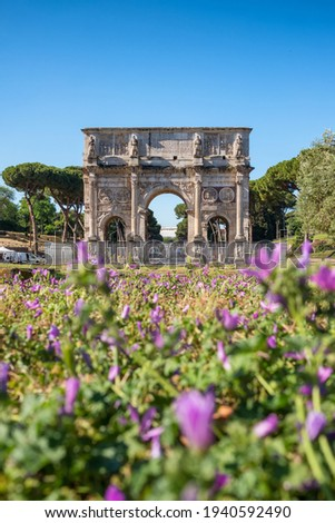 Arch of Titus or Arco di Tito in Rome, Italy. Historical landmark of Rome. Ancient ruins of Triumph arch with flowers at foreground Stock fotó ©