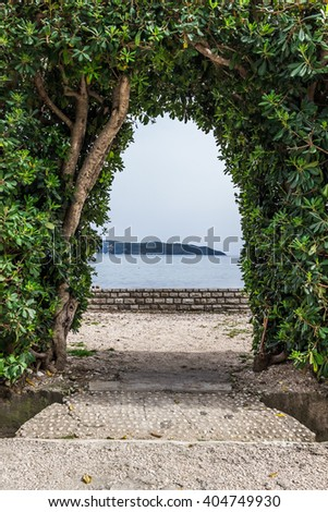 stock photo arch of trimmed plants with a sea and mountains view in monteneg 404749930 - Каталог — Фотообои «Балконы, арки»