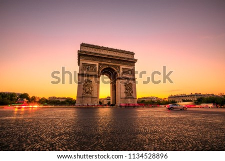 Arch of triumph at twilight. Arc de Triomphe at end of Champs Elysees in Place Charles de Gaulle with cars and trails of lights. Popular landmark and tourist attraction in Paris capital of France. #1134528896