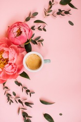 Arch shape of delicious fresh morning espresso coffee, eucalyptus leaves and blossoming coral peonies on the tender pink background, top view, flat lay