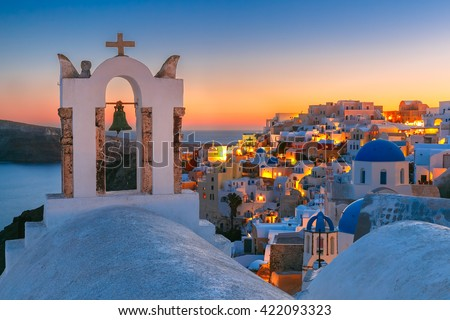 Arch with a bell, white houses and church with blue domes in Oia or Ia at sunset, island Santorini, Greece