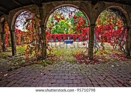 Arch with red flowers - stock photo