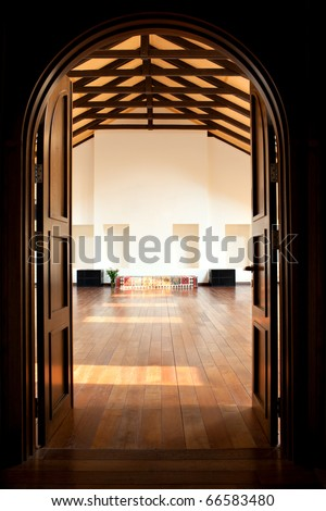Arch with two doors leading into a large light hall