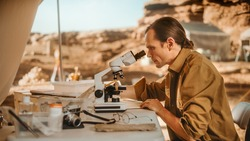 Archaeological Digging Site: Great Male Archaeologist Doing Cultural Research, Discovers Ancient Civilization Historical Artifacts, Fossil Remains at Excavation Site, Study it Under Microscope