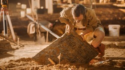 Archaeological Digging Site: Great Male Archeologist Work on Excavation Site, Carefully Cleaning, Lifting Newly Discovered Ancient Civilization Cultural Artifact, Historic Clay Tablet, Fossil Remains