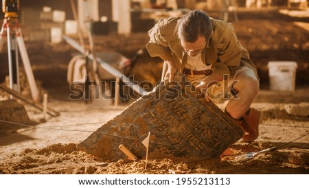 Archaeological Digging Site: Great Male Archeologist Work on Excavation Site, Carefully Cleaning, Lifting Newly Discovered Ancient Civilization Cultural Artifact, Historic Clay Tablet, Fossil Remains Zdjęcia stock ©
