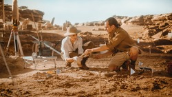 Archaeological Digging Site: Two Great Paleontologists Cleaning Newly Discovered of Dinosaur. Archeologists on Excavation Site Discover Fossil Remains of New Species Skeleton. Close-up Focus on Hands