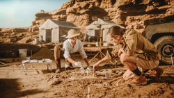 Archaeological Digging Site: Two Great Paleontologists Discovered Fossil Remains of Prehistoric Dinosaur, Clean it with Brushes. Archeologists Work on Excavation Site, Discover New Species Bones