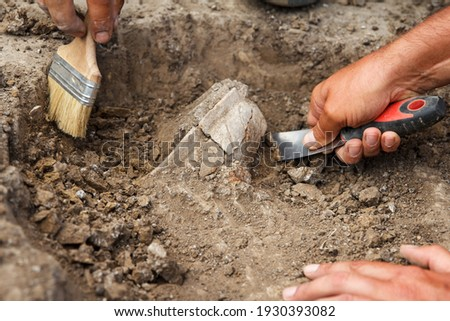 Archaeological excavations, archaeologists work, dig up an ancient clay artifact with special tools in soil Foto stock ©