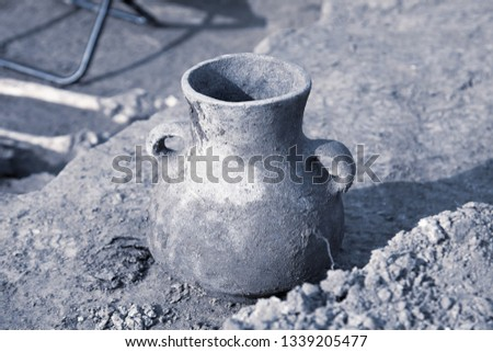 Archaeological excavations. Found artefact, aged damaged ceramic jar on the ground, human remains on a background. Real digger process. Outdoors, copy space, close up, cool monochromatic tone. #1339205477