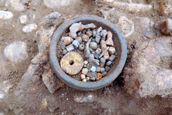 Archaeological excavations. Human remains (bones of skeleton ) on the ground and little artefacts found in the tomb (beads and parts of ancient decorations). Outdoors, close up, copy space.