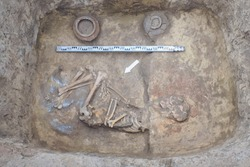 Archaeological excavations. Top view of the burial of a person, bones, skull with two ritual ceramic pots and a scale ruler.