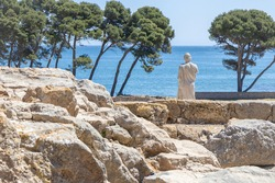 Archaeological Remains of ancient city Empuries with reproduction of the statue of Aesclepius on the remains of a Greek rampart. Archaeology Museum of Catalonia, Spain.
