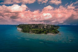 Archaeological site of Grotte di Catullo, Sirmione, Italy early morning aerial view. lake garda. Cumulus pink clouds, Grottoes of Catullus and the Archaeological Museum of Sirmione.