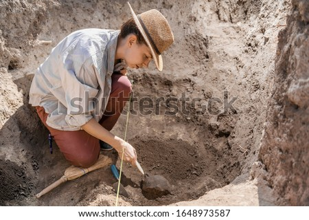 Archaeologist digging with hand trowel, recovering ancient pottery object from an archaeological site. Foto d'archivio ©