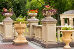 Arched balcony with balustrade and flower vases. Elements of architectural decorations of buildings, balconies railings and balustrade.  stone flower pot with blooming flowers on the railing. granit.