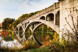 Arched cement bridge over Lake Ontelaunee closed to traffic pictured against fall foliage