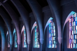 Arched columns in monastery chapel with stained glass windows