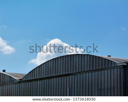 arched corrugated aluminum clad hangar type building top detail. blue sky with white clouds. low angle view. film studio like design. movie studio concept. airport hangar. studio hangar. movie making