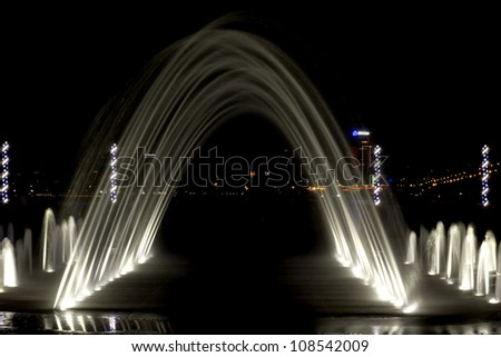 arched fountain in the background of  city at night, backlit closeup