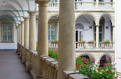 Arched gallery with columns and balustrade decorated with flower pots with flowers in the courtyard of an old building, view from the second floor