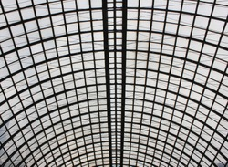 Arched glass roof top close up view in modern building. Urban architecture of ceiling with see through panels