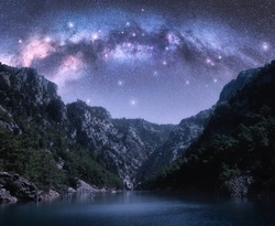 Arched Milky Way and stars over beautiful mountains and sea at night in summer. Colorful landscape with purple starry sky with bright Milky Way arch, constellation, water. Galaxy. Nature and space